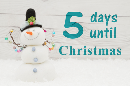 Christmas countdown message, Some snow and a snowman on weathered wood with text 5 days until Christmas
