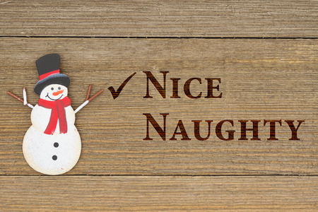 naughty or nice: Old fashion Christmas message, A retro snowman on weathered wood background with text Nice Naughty Stock Photo