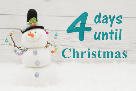 Christmas countdown message, Some snow and a snowman on weathered wood with text 4 days until Christmas