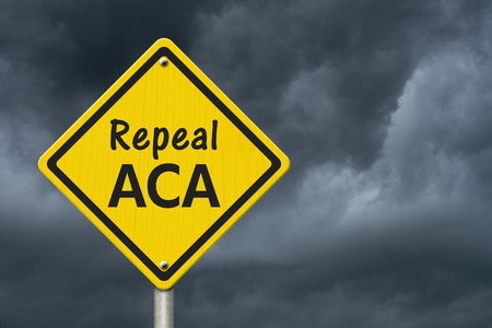 Repealing and replacing the Affordable Care Act healthcare insurance, Yellow warning highway road sign with words repeal ACA with stormy sky background
