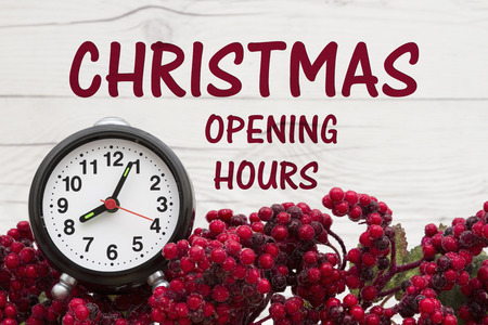 Ouderwetse Kerstmis store bericht, Frost gedekt holly rode bessen met een wekker op verweerde houten achtergrond met tekst opening kerst uur