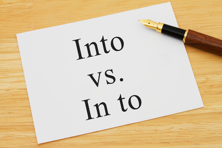 grammatical: Learning to use proper grammar, A white card on a desk with a pen with words Into vs In to Stock Photo