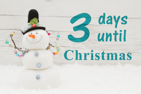 Christmas countdown message, Some snow and a snowman on weathered wood with text 3 days until Christmas Banco de Imagens