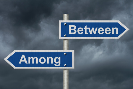 grammatical: Learning to use proper grammar, Blue road sign with words Between and Among with stormy sky background