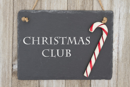 holiday budget: Old fashion Christmas savings plan message, A retro chalkboard with a candy cane hanging on weathered wood background with text Christmas Club