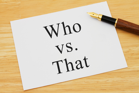 grammatical: Learning to use proper grammar, A white card on a desk with a pen with words Who vs That