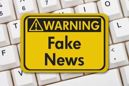 señal de alerta de noticias falsas, Una señal de advertencia de color amarillo con el texto noticia falsa en un teclado Foto de archivo