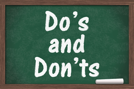 grammatical: Learning to use proper grammar, Chalkboard with a piece of chalk and text Dos or Donts Stock Photo