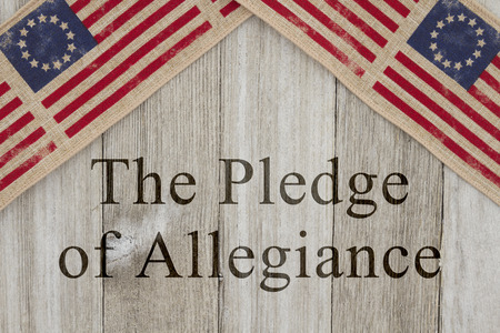 allegiance: America patriotic message, USA patriotic old flag on a weathered wood background with text The Pledge of Allegiance Stock Photo