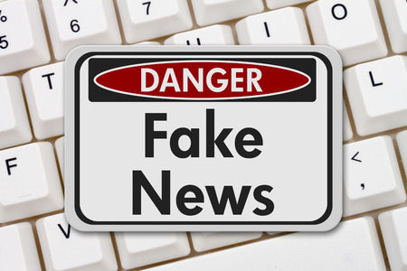 Fake news danger sign, A black and white danger sign with text Fake News on a keyboard