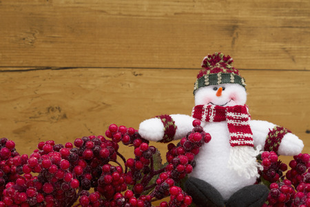frost covered: Old fashion Christmas berry background, Frost covered red holly berries with a snowman on weathered wood background with copy space for your message