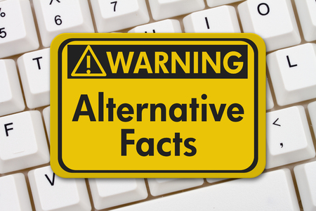 disinformation: Alternative Facts warning sign, A yellow warning sign with text Alternative Facts on a keyboard Stock Photo