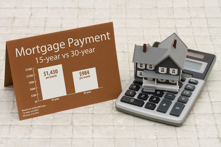 Learning about mortgage payments, House on a calculator with a card and an infographic on the mortgage payments