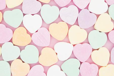 Old fashion pale multi colored candy heart background Foto de archivo