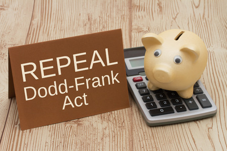The Dodd-Frank Act, A golden piggy bank, card and calculator on a wood desk with text Repeal Dodd-Frank Act