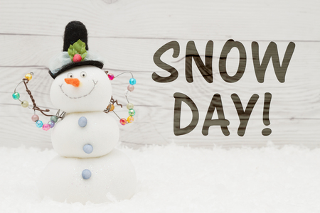 Snow day message, A snowman with text Snow Day on weathered wood Stock Photo