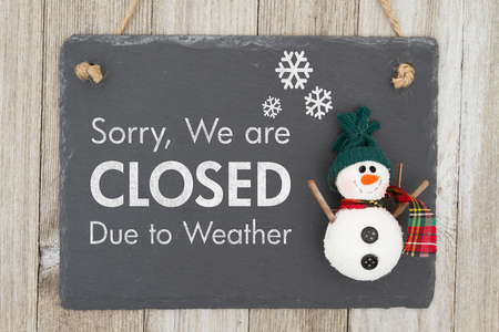 Closed due to weather sign, A chalkboard sign with a snowman with text Closed due to weather on weathered wood Imagens