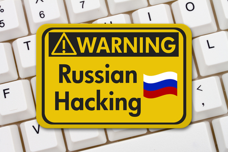 computers online: Russian hacking warning sign, A yellow warning sign with text Russian hacking on a keyboard Stock Photo