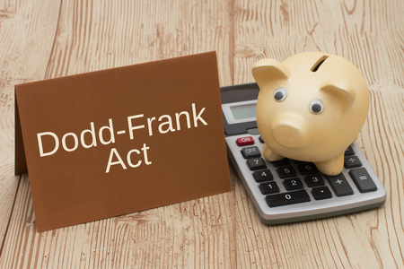 The Dodd-Frank Act, A golden piggy bank, card and calculator on a wood desk with text Dodd-Frank Act 版權商用圖片