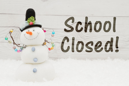 School canceled message, A snowman with text School Closed on weathered wood