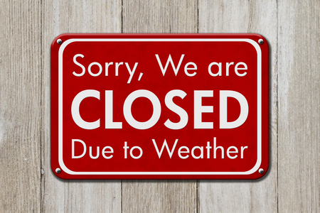 Closed due to weather sign, A red sign with text Sorry we are closed due to weather on weathered wood