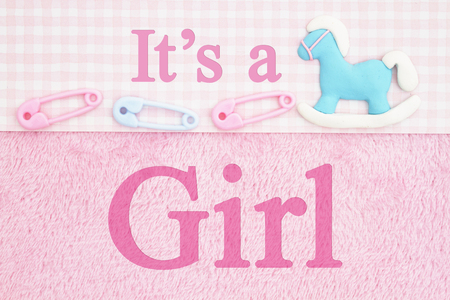 Old fashion Its a girl message, Baby diaper pins and a hobby horse with pink fabric background and text Its a Girl