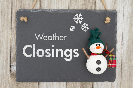 Weather closing sign, A chalkboard sign with a snowman with text Weather Closing on weathered wood
