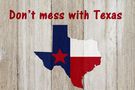 A rustic patriotic Texas message, Map of Texas with the Texas Flag colors on weathered wood background with text Don't mess with Texas Stockfoto