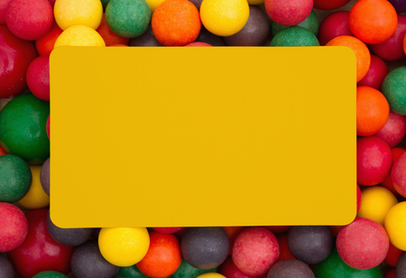 multicolored gumballs: Colorful multi colored bubble gum background with yellow card Stock Photo