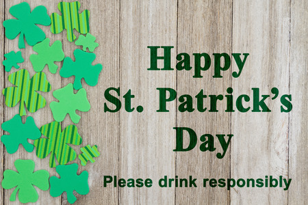 drink responsibly: Saint Patricks Day safety message, Green shamrocks on weathered wood with text Happy St Patricks Day Please drink responsibly