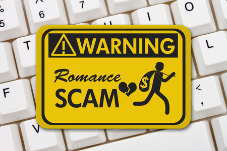 con man: Romance Scam warning sign, A yellow warning sign with text Romance Scan and theft icon on a keyboard Stock Photo
