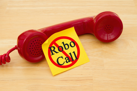 Stop getting a call from a Robocall, Retro red phone handset with a yellow sticky note and text Robocall with not icon 写真素材