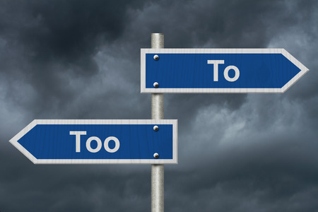 grammatical: Learning to use proper grammar, Blue road sign with words To Too with stormy sky background