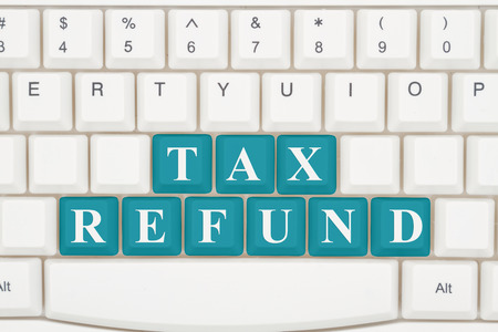 website words: Preparing your taxes on the internet, A close-up of a keyboard with teal highlighted text Tax Refund