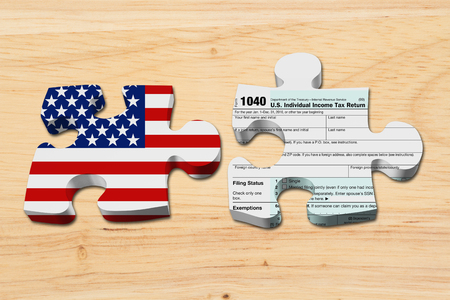 understand: Understanding how to do your taxes, Two puzzle pieces with the flag of the USA and a US Federal tax 1040 income tax form on wood