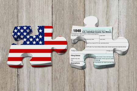 Understanding how to do your taxes, Two puzzle pieces with the flag of the USA and a US Federal tax 1040 income tax form on weathered wood Imagens