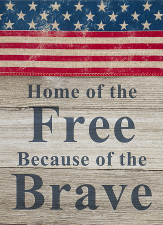USA patriotic message, USA patriotic old flag on a weathered wood background with text Home of the Free Because of the Brave