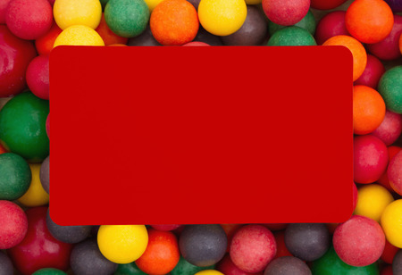 multicolored gumballs: Colorful multi colored bubble gum background with red card Stock Photo
