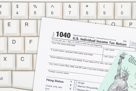 a us federal tax 1040 income tax form with refund check on a keyboard photo - Federal Tax Form