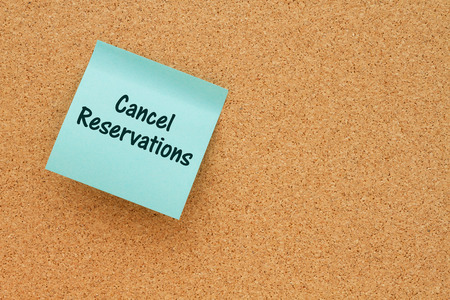 A reminder to cancel reservations, Bulletin board with a teal sticky note with text Cancel Reservations