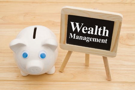 Learning how to manage your wealth, A piggy bank on a desk with chalkboard with text Wealth Management