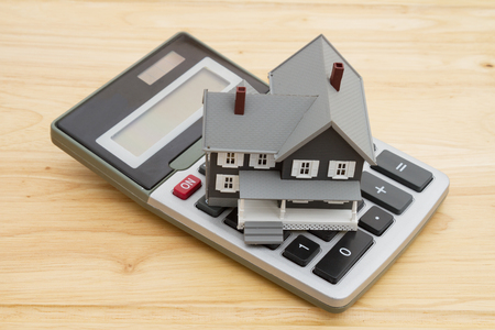 business loans: Mortgage calculations for your home, A house with a calculation on a wood desk
