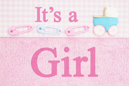 Old fashion Its a girl message, Baby diaper pins and a baby carriage with pink fabric background and text Its a Girl Banco de Imagens