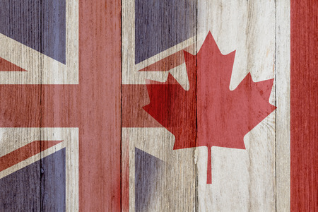 allies: Relationship between the Britain and Canada, The flags of Britain and Canada merged on weathered wood Stock Photo