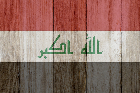 weathered: A rustic old Iraqi flag on weathered wood for a background
