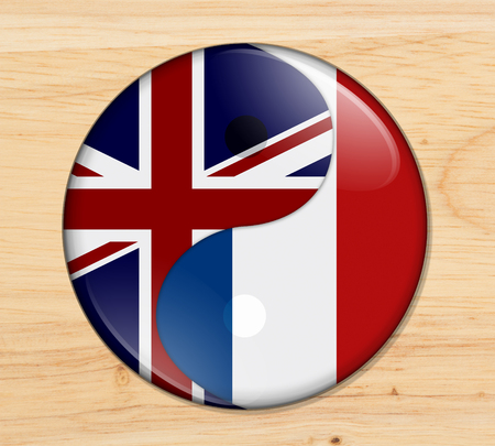 Britain and France working together, The British flag and French flag on a yin yang symbol on wood Reklamní fotografie