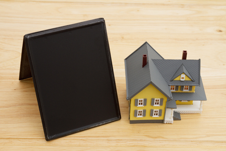 blank spaces: A house with retro freestanding chalkboard on a wood desk that is blank for your message