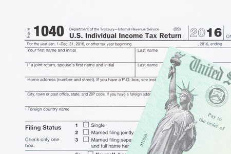 A US Federal tax 1040  income tax form with money and refund check Stock Photo