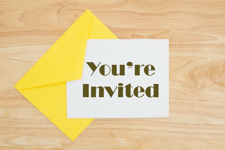 An invitation, An embossed white card with yellow envelope on a desk with text Youre Invited Stock Photo