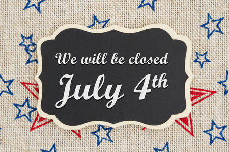 We will be closed July 4th text on a chalkboard with patriotic USA red and blue stars on burlap